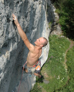 Rock climber on a cliff face that contains fossils