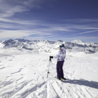 Female skier stopping to appreciate a magnificent view across the French Alps